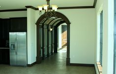 Arched doorway and rustic trim. Arch Doorway, Tuscan Design, Custom Homes, Orlando, Tall Cabinet Storage, Building A House, Florida, Rustic, Board