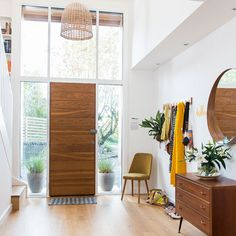 Modern Oak front door, light and airy entrance hall, round Stockholm mirror from Ikea. Scandinavian style hallway.