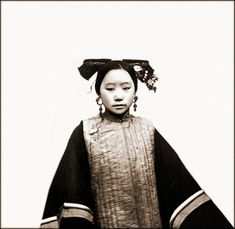 This is a photo of a Manchu woman that was taken in 1869 by a man named John Thompson who took many photographs of the many 19th century Chinese women. This was the typical fashion of Manchu women....