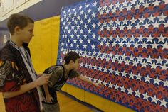 Teaching Kids About Veterans Day: Woodbrook Middle School students, Noah Allen (left) and Cory Goodnight look for the names of military family members or relatives they wrote on stars for the school's American Flag display for Veteran's Day 2010.