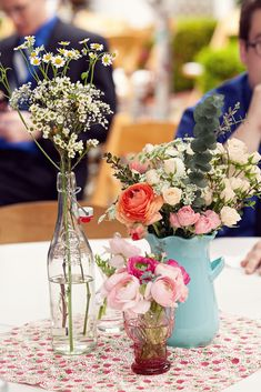 The combination of various bottles and vases creates a sweet table centerpiece.