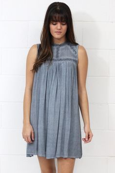 Sleeveless shift dress with lace trimmed details around the neckline and on seams of dress. Fully lined, non-sheer. Pigment washed dress which gives it a two-tone look. Grey in color. Buttons at back of neck.
