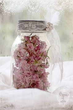 Dried flowers in clear canning jar with tulle ribbon for vintage wedding reception table décor.