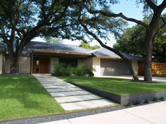 @Austin Living: metal to level the yard, concrete walkway, rocks around trees, roof.