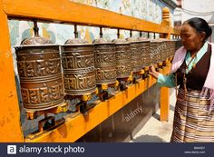 Download this stock image: tibetan lady spinning prayer wheels at boudhanath ,one of the holiest Buddhist sites in Kathmandu, Nepal - BMA3D1 from Alamy's library of millions of high resolution stock photos, illustrations and vectors.