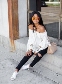 With a crochet off-the-shoulder top, slim black jeans, and mirrored sunglasses