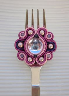 Soutache ring in pink, purple and plum, with a glass centre