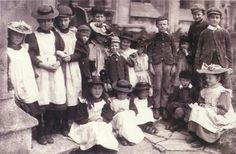 This group of working class children shows a variety of hats and pinafore dresses on the girls, with the boys in long trousers, buttoned jackets and white collared shirts. (1890)