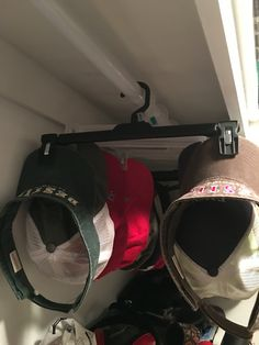 Men and there hats use those hanger you get when you buy clothes and hang two-hats per hangers and hang on rack in closets BAM  there out of your way