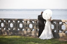 Gatsby Inspired Wedding. Wedding Planning, Event Design & Production by Swank Productions at Hempstead House at Sands Point Preserve, www.swankproductions.com  Bride & Groom looking at views of the water on castle lawn with parasol Photo by Mel Barlow   #wedding #design #gatsby #melbarlow