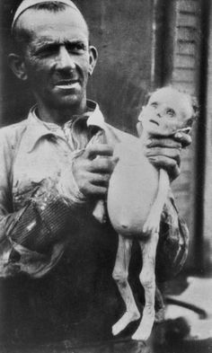 Unknown prisoner in the Warsaw ghetto holding a dead body, swollen from hunger baby.