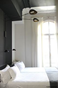 Crisp white with dark grey walls. Love this combo. Looks great in this bedroom. That wall light is pretty cool too.