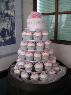 White chocolate mudcake layered with white chocolate ganache  Cupcakes are also white mudcake and covered with buttercream.  Roses on cupcakes and roses made with modelling paste  Cake has been set up ontop of an old wine barrel