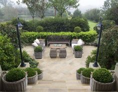 Garden designed by Marco Meneguzzi- via The Creeping Fig-Love the gray baskets with boxwoods.