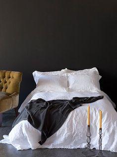 Een witte slaapkamer met één donkere muur. Door deze te stylen met de juiste accessoires is het in de winter  cosy & chic en in de zomer fris en licht door te spelen met het contrast.