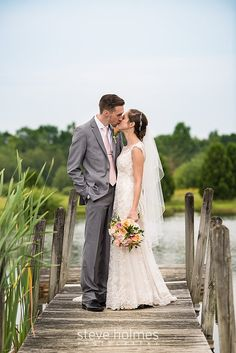 Groom leans in to kiss his new bride on the dock of a summer pond. Photo by Steve Holmes Photography
