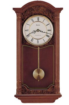 """Solid Oak front in a dark red oak finish. This classic wall clock is sure to highlight any home or office with burl finish accents and recessed glass side panels. Switchable Westminster or Whittington melody movement with a night shut-off option and adjustable volume control. Size: 23"""" H x 11.75"""" W x 4.75"""" D"""