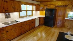 1950s knotty pine kitchen updated with solid surface white countertops and subway tile backsplash