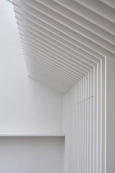White ribbed panelling provides a neutral backdrop for smoked-oak furnishings and marble bathrooms in this former west London office by Mclaren Excell