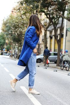 Aida Domenech wears a pair of white All Stars with rolled up denim jeans and a funky blue coat