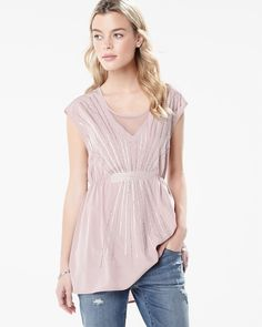 Add a flowy layer with this short sleeve chiffon tunic with beaded front embellishment and see-through V-neckline.<br /><br />- Cinched waist<br />- Knit back<br />- Mesh insert at the neck