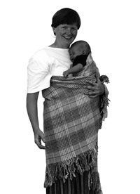 """""""The traditional Welsh nursing shawl, siol fagu, is made of pure wool Welsh flannel. It is six feet square, including six inch fringes on all four sides. Nursing shawls were a staple product of the Welsh woollen mills. The shawls are practical for carrying a baby, the baby being held in front, high up, with the mother's right arm free, the left arm helping support the baby but still useful. It provides warmth for the baby and mother, and easy communication between them."""""""