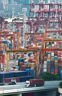 """Cargo containers stacked up at a port ... In English, """"shipping"""" means to send something from one place to another ... by ship, truck or plane ... we still use the word """"ship"""" ..."""