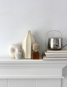 At home with a bit of sun and a collection of things including a watering can and books on our mantle.