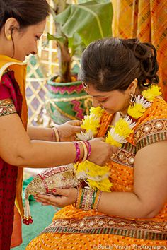 The Bride Is Showered With Wreaths Of Flowers During Turmeric Ceremony