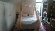 My bed with sheer curtains fairy lights cream and gold and red decorating