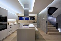 Kuchyň je zhotovena na míru danému prostoru z lakované MdF desky v béžovém odstínu. digestoř je obalena do hnědého skla, z něhož je také stěna s nenápadnými dveřmi do spíže. Hnědé zabarvení má i pracovní deska z materiálu technistone. barové židle zde nahrazuje vysoká lavice