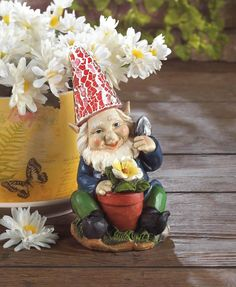 Here's a happy gardener who's ready to add some cheery light to your yard. This adorable gnome is proudly tending to his yellow bloom, and his red hat will shine bright at night thanks to the statues