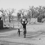 MALI. Dogon region. Igeli. Woman carrying water and child on the way to their house. 2009.