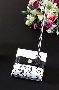"Lillian Rose Black & White Pen Set This pen set includes a silver pen with black ink and a 3.75"" x 3.75"" white satin pen base. The base is decorated with a black satin ribbon, black satin bow and circular rhinestone ornament. Below the ribbon is a silkscreened black pattern of swirls, leaves and flowers. A matching guest book is sold separately. Also available in red. Price $17.90"