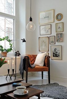 Living room: White walls and floor boards, orange arm chair, grey carpet, gold picture frames and low lying light bulb: