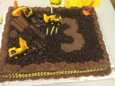 Construction theme Birthday cake.Semi-home made. Used a store bought Costco cake. Crumbled and grinded chocolate Oreos. Mini construction vehicles purchased at Toys R Us. Added some pieces from a favor bag purchased at Party City. Chocolate tools were a find at CVS and some Kit Kats. Construction ribbon came with gift wrap purchased on Amazon. To make the 3-cut out a 3 on wax paper and laid cookie down and removed the wax paper. Took off wax paper after I got it to the party location.