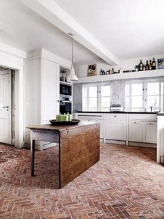 Gorgeous kitchen; I love that herringbone-patterned floor, and that table is super special.