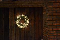 One of my wreaths under a hand hewn barn beam on one of my barn board walls near the chimney.