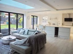 Scandinavian inspired white modern contemporary open plan kitchen living room with bi folding doors.