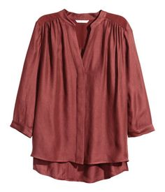 Wide, V-neck blouse in woven fabric with a slight sheen, with concealed buttons at the front, contrasting satin yoke, 3/4-length sleeves with buttons at the cuffs and short slits in the sides. Slightly longer at the back.