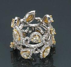 A colored diamond and diamond foliate eternity band. photo Bonhams    estimated total diamond weight: 3.90 carats; mounted in eighteen karat bicolor gold;