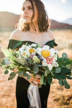"""This bouquet has """"krinkled"""" peonies that have white petals and a yellow center, and is surrounded by leafy greenery. This perfectly complements the brides dark green wedding dress. It is a beautiful look for an alternative bride looking to get away from tradition for a summer wedding. You can even use this look as inspiration for your bridesmaid dresses and bouquets! Here are more peony wedding bouquets. // Photo: Lauren Wrigley Photography and Florals: Jocelyns Florals"""