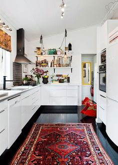 Bring a contemporary vibe to your kitchen by using BEHR paint in Ultra Pure White on the walls, and even the cabinets, to make your home decor pop. Add an intricate Aztec rug over your black floors to tie this look together.