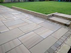 Sawn rainbow sandstone patio with sett edging and steps by SilverBirch Gardens Ltd