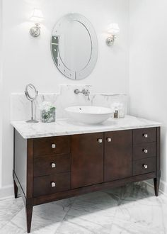 Chic, elegant bathroom features pale, pale grey wall lined with an oval vanity mirror illuminated by polished nickel sconces over a dark brown footed washstand topped with white marble and a white porcelain bowl sink under a wall-mount faucet alongside a marble tiled floor laid out in a diamond pattern.