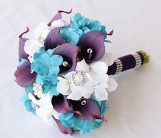 This is a perfect bouquet with Off White Roses and Teal Turquoise Hydrangeas mixed with Deep Purple Calla Lilies and accented with Crystals and