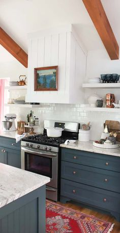 From the slate blue cabinets and marble countertops, to the exposed wood beams and bright open shelving, everything about this stylish kitchen will have you inspired. If you're renovating the heart of your home, make sure to check out this beautiful space.