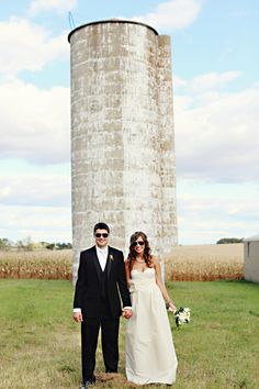 bride and groom wearing sunglasses and standing in front of a silo   fun shot at farm country wedding   photo: www.eyespy-weddings.com.. We could do this in front of the grain tank