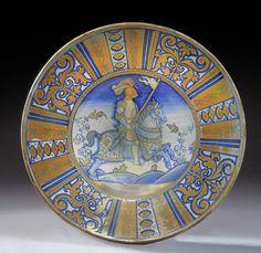 PLAT EN MAJOLIQUE DE DERUTA,VERS 1530-1550  A décor bleu et ocre lustré au centre d'un cavalier en armure de profil, portant un étandart, l'aile décorée de rinceaux feuillagées et motifs géométriques dans des compartiments ; restauré, manques à la base  Diamètre : 39,5 cm. (15 ¼ in.)