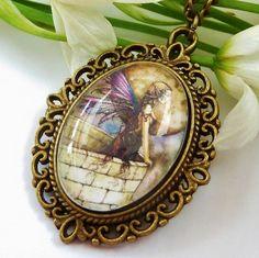 Halskette im Vintage-Stil mit schönem Elfen-Motiv.  Die Kette besteht aus einer antikgoldfarbenen Metallfassung und einem handgearbeiteten Glas-Caboch